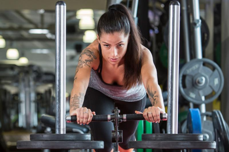Lady pushing weights on a sled track in the gym during a T30 class