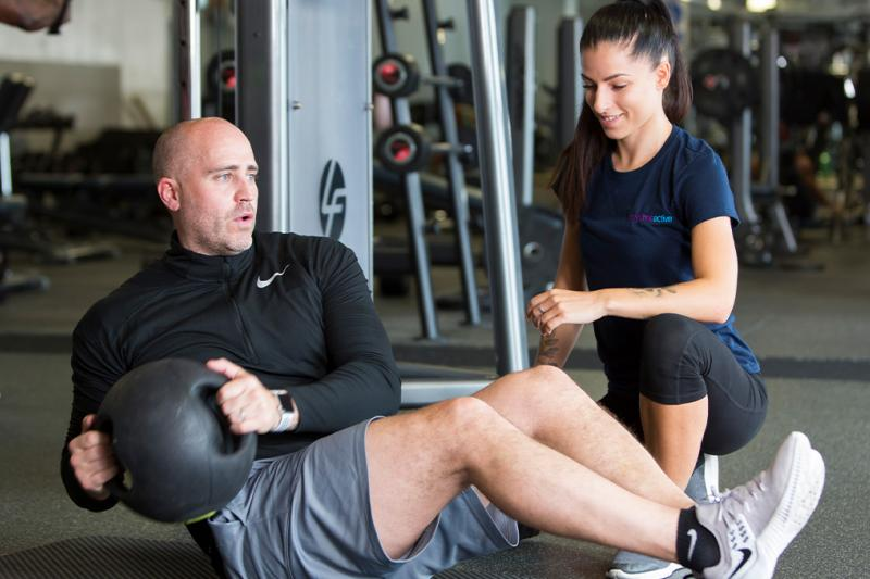 A challenge seeker with a personal trainer working out in the gym