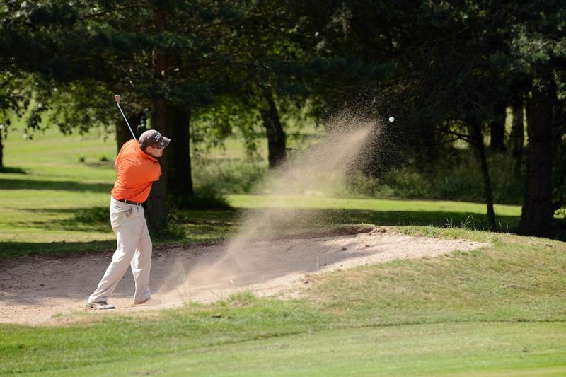 Man hitting a bunker shot on a golf course