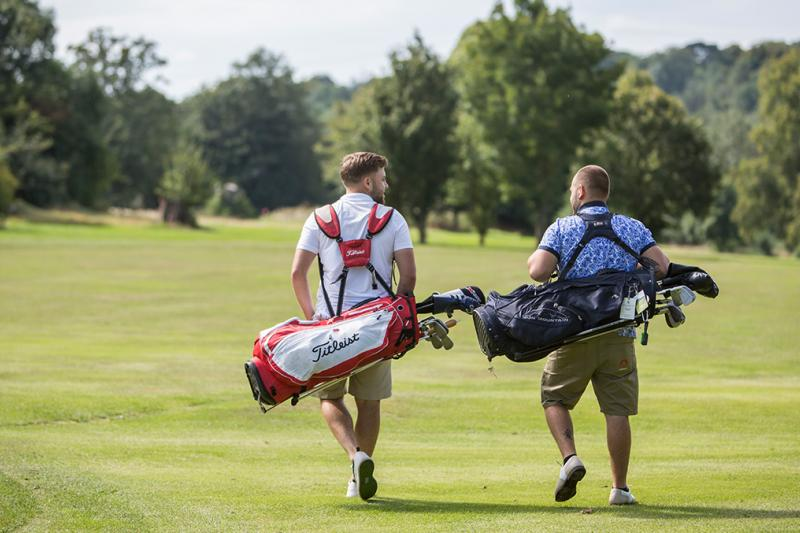 Men walking with golf bags on a golf course