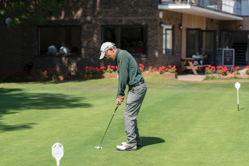 Man practicing putting on a putting green at a golf course