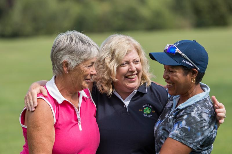 Friends playing golf together smiling.