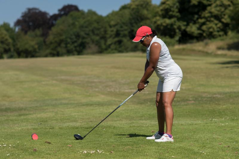 A lady taking a tee shot on the golf course