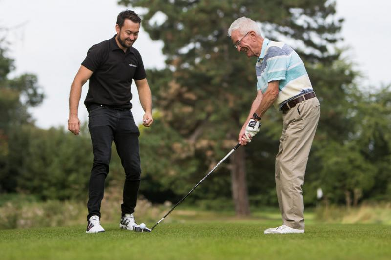 Man smiling on a tee having a golf lesson