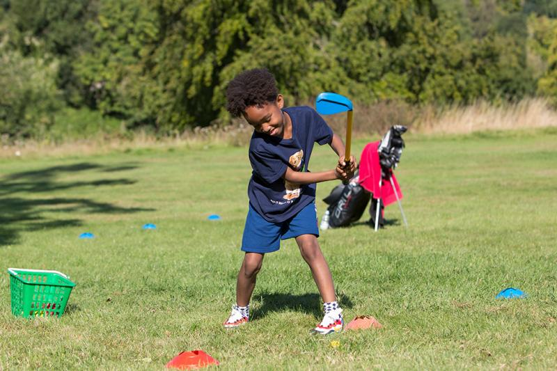 A young boy hitting a golf ball in a junior golf lesson