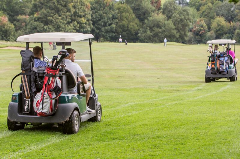 Golfers driving golf buggies