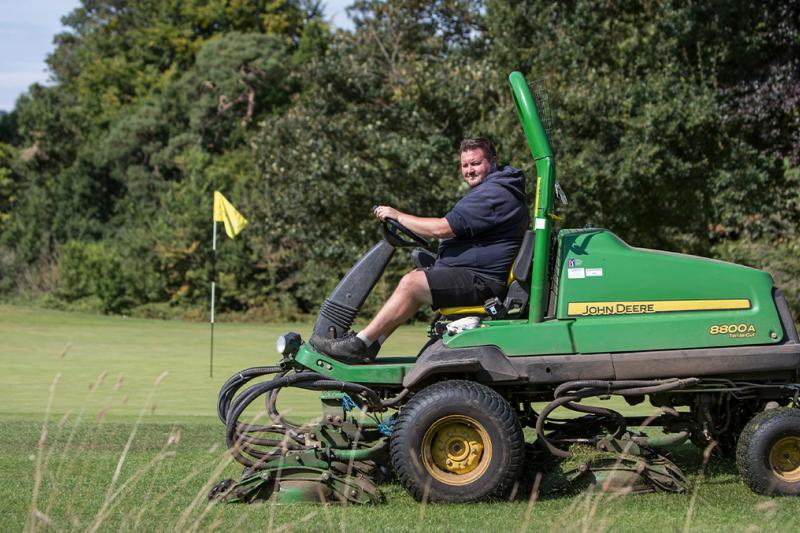 A greenkeeper on a lawnmover working at a golf course
