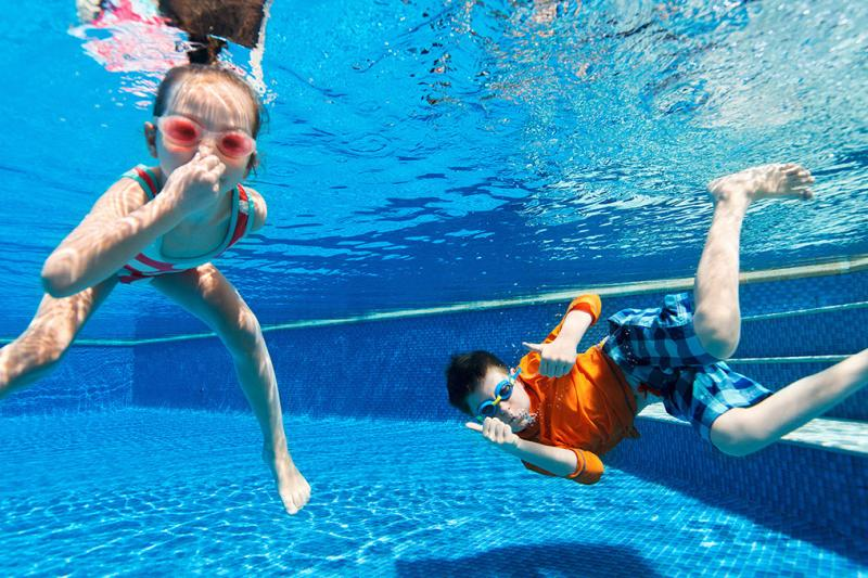 Children holding their breath underwater at a swimming pool