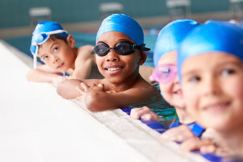 Children in swimming caps enjoying a swimming lesson