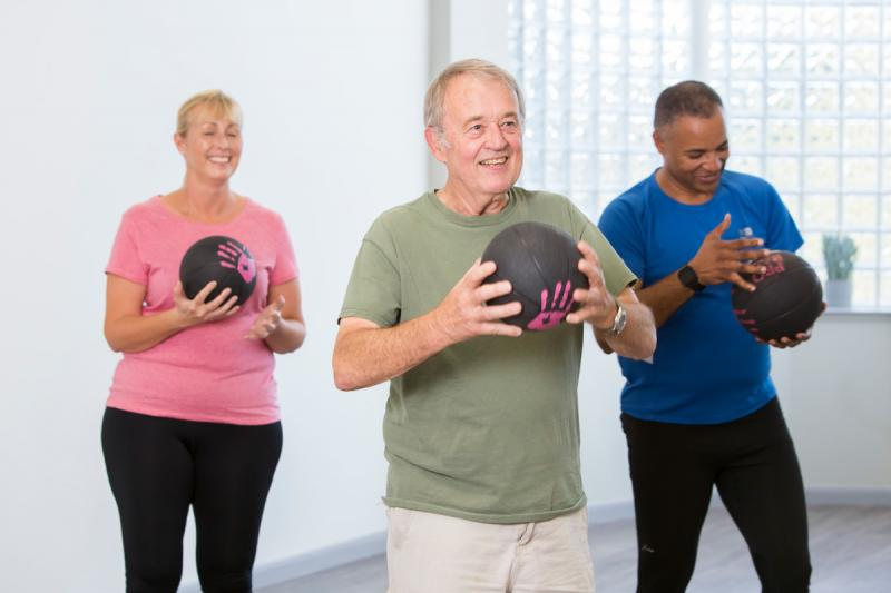 Group of people exercising with weighted balls