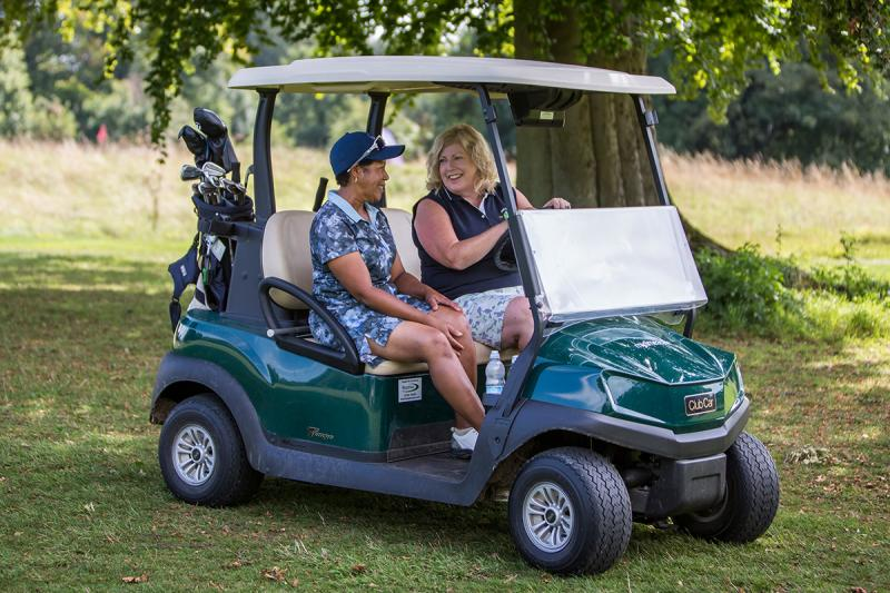 Two ladies playing golf driving a golf buggy